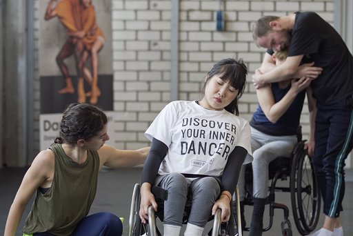 A dancer in a wheelchair closes her eyes and sways to one side with a dancer on the floor reaching her arm towards her
