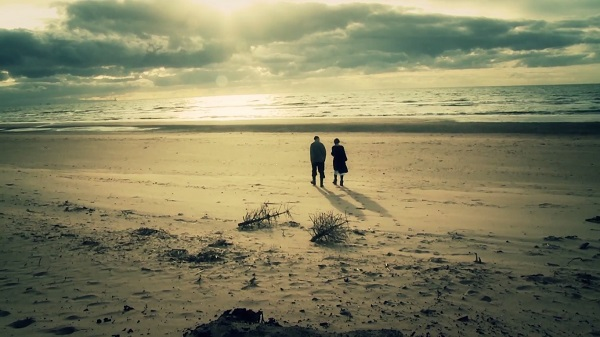 Screen grab showing two people walking on a beach