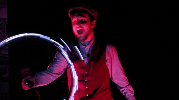Young man in waistcoat and flatcap spins a bicyclewheel, lighting up the rim