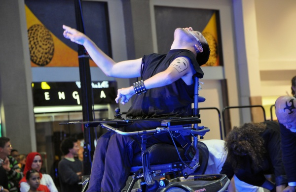 Photo of a wheelchair-user performing on stage