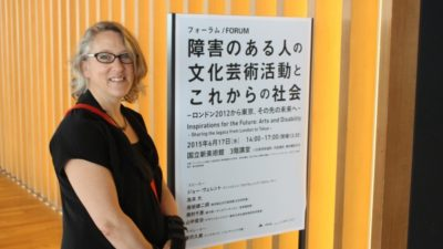 Photograph of Jo Verrent stnading next to a sign at a conference in Japan.