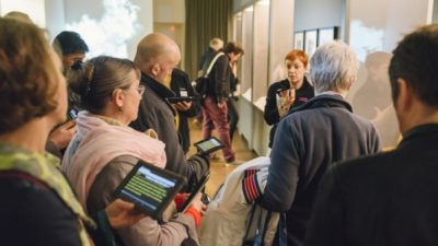 A group of people using Stagetext-enabled devices to look around an exhibition