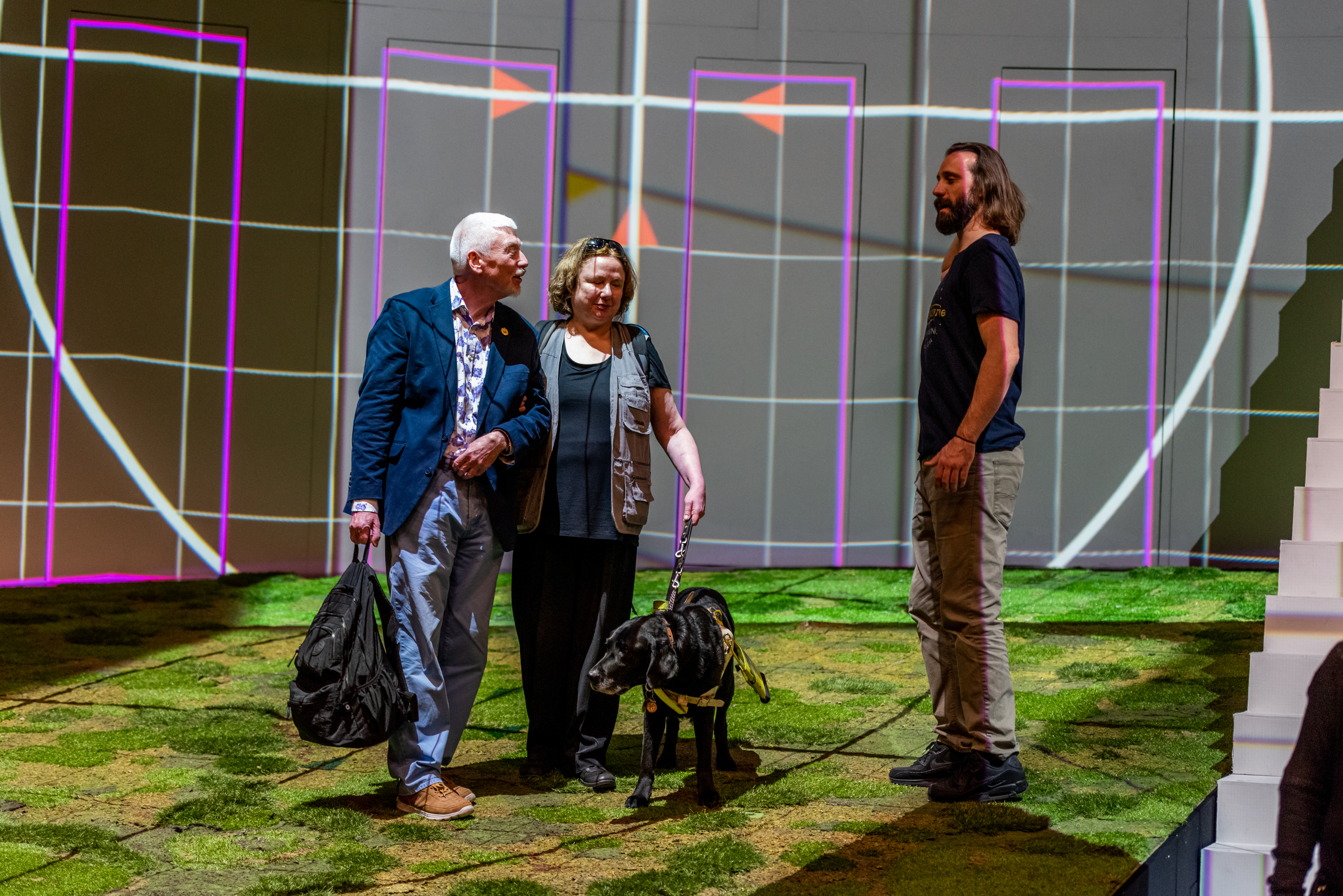 Man and woman with a guide dog on a stage