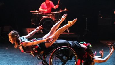 A female dancer lies mid-air across a dancer in a wheelchair who is bent over backwards, their arms stretched out. A drummer plays in the background.