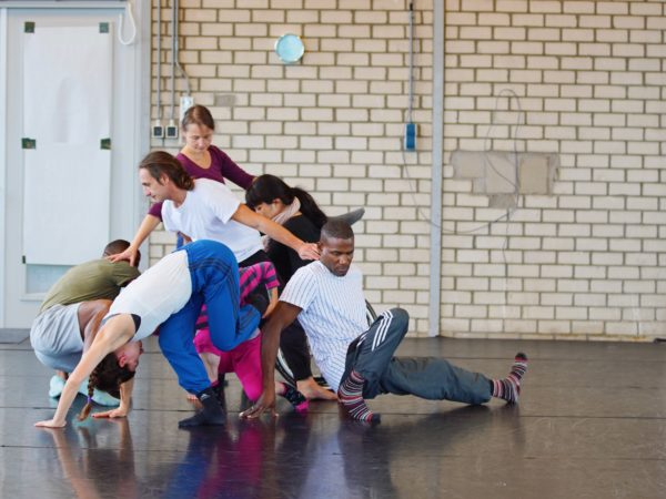 An international gathering of artists create a complicated group structure by intertwining their bodies in a dance studio.