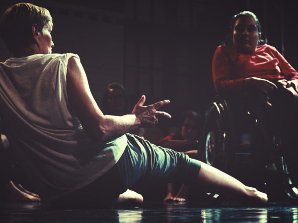 A dancer leans back on the floor welcoming a dancer using a wheelchair to dance with them.