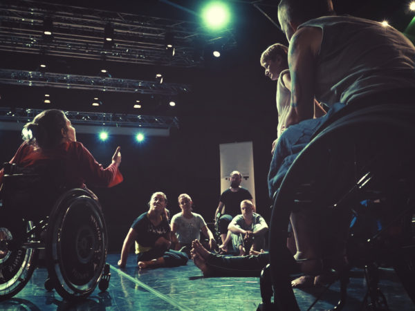 An artist in a wheelchair addresses a group of artists gathered round to listen