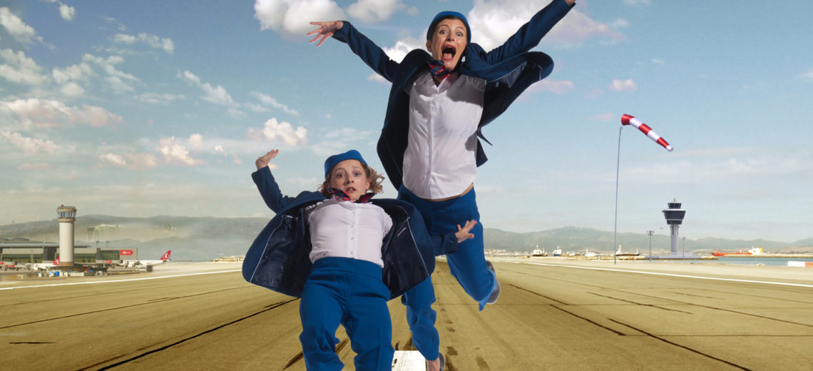 Two dancers dressed as flight attendants run as if an aeroplane is coming in to land
