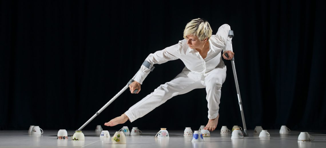 A Woman using crutches dances on tea cups