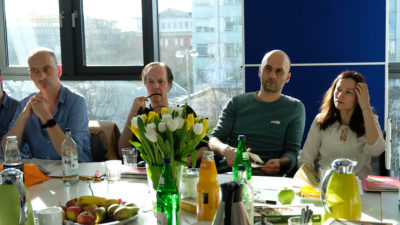 Four people sit at a table in a meeting, with food and drink on the table