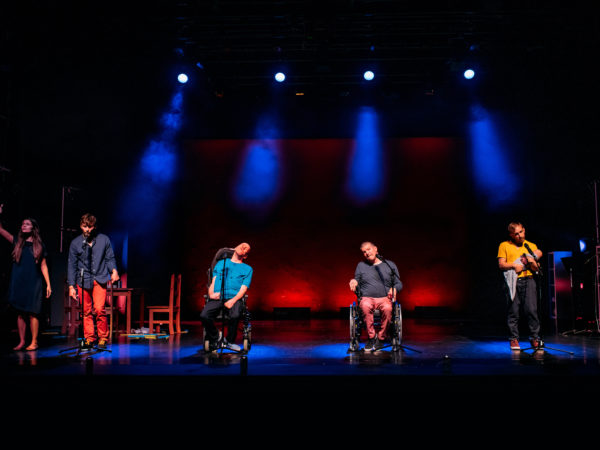 5 performers on a colourfully lit stage