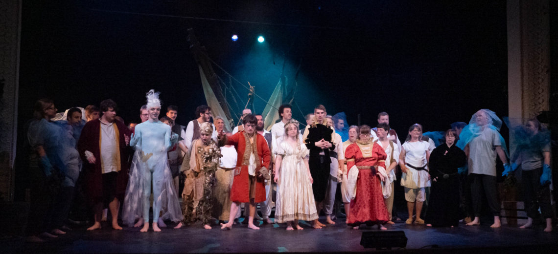 This photograph shows the large enseble cast of Blue Apple's show, The Tempest, taking applause from the audience