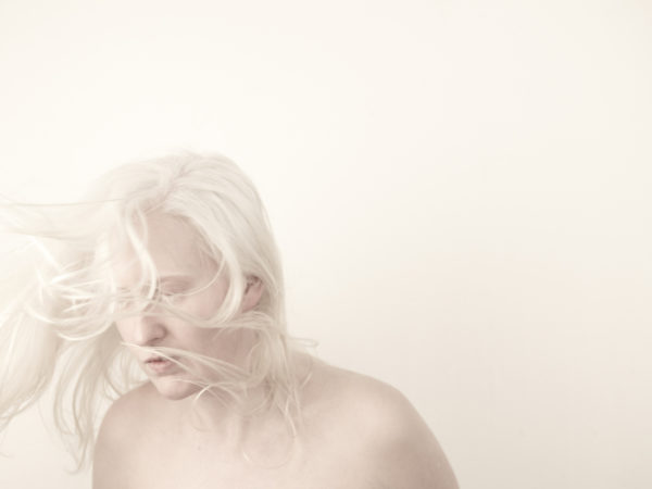 An artist with very white hair and pale skin looks away, pictured against a stark white background