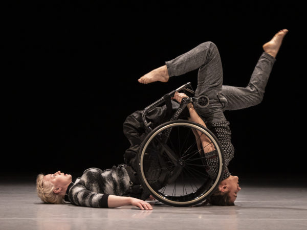 Two female performers, one with blonde hair uses a wheelchair and lies with her back on the floor, the other stands upside down with her legs cycling in the air