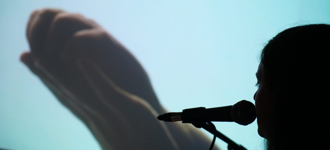 Projection of two hands together with blue background, in foreground is head of female performer facing the projection with microphone.