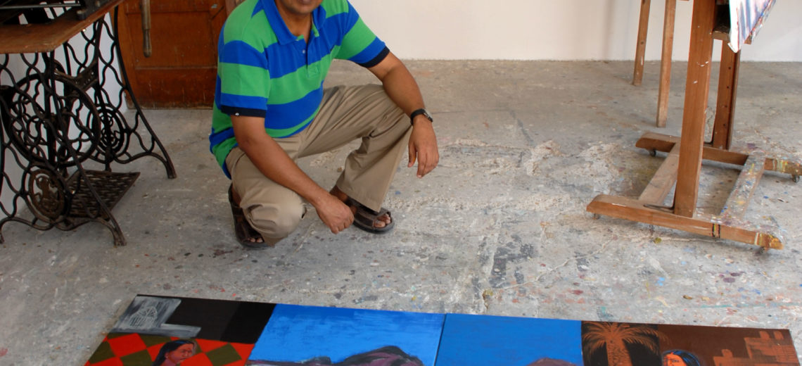 Man crouching by his paintings on the floor