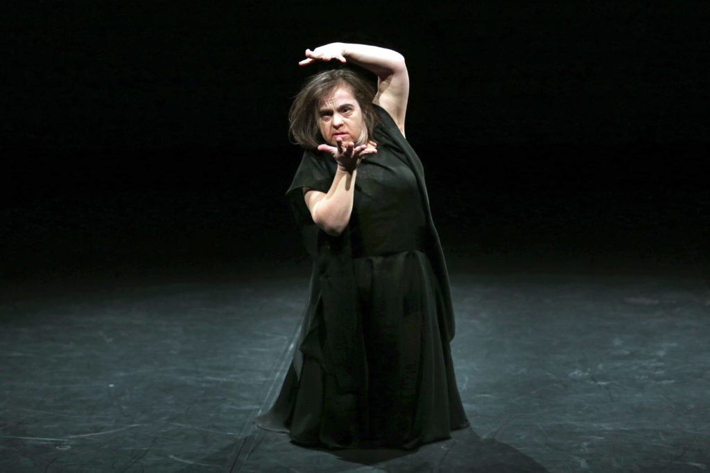 Learning disabled female performer dressed all in black gestures with hands