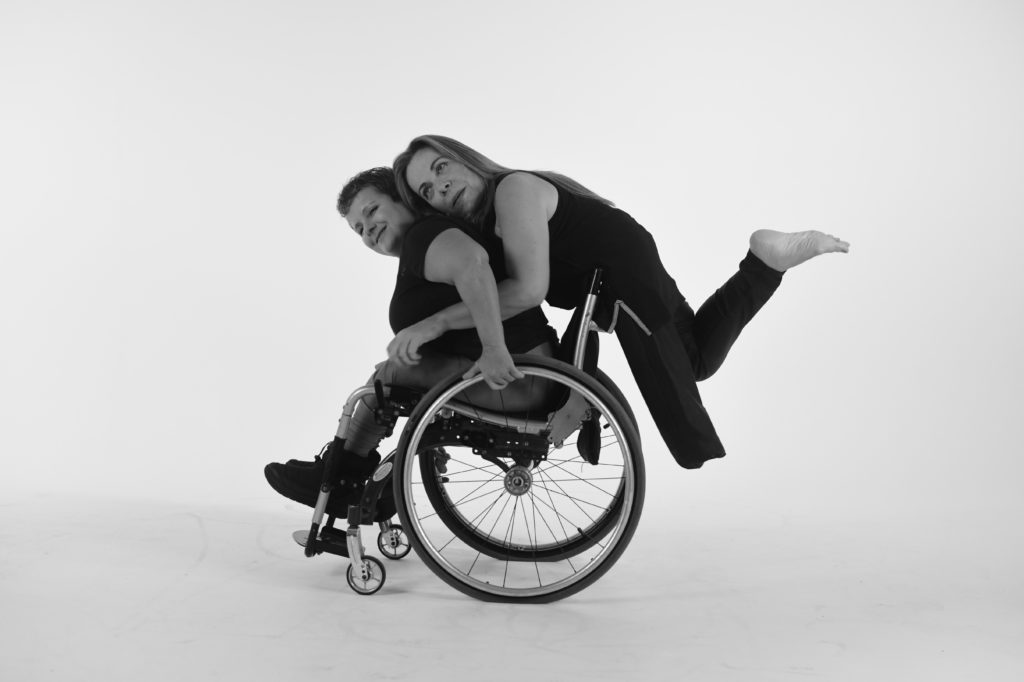 A female amputee performer embraces a performer in a wheelchair from behind.