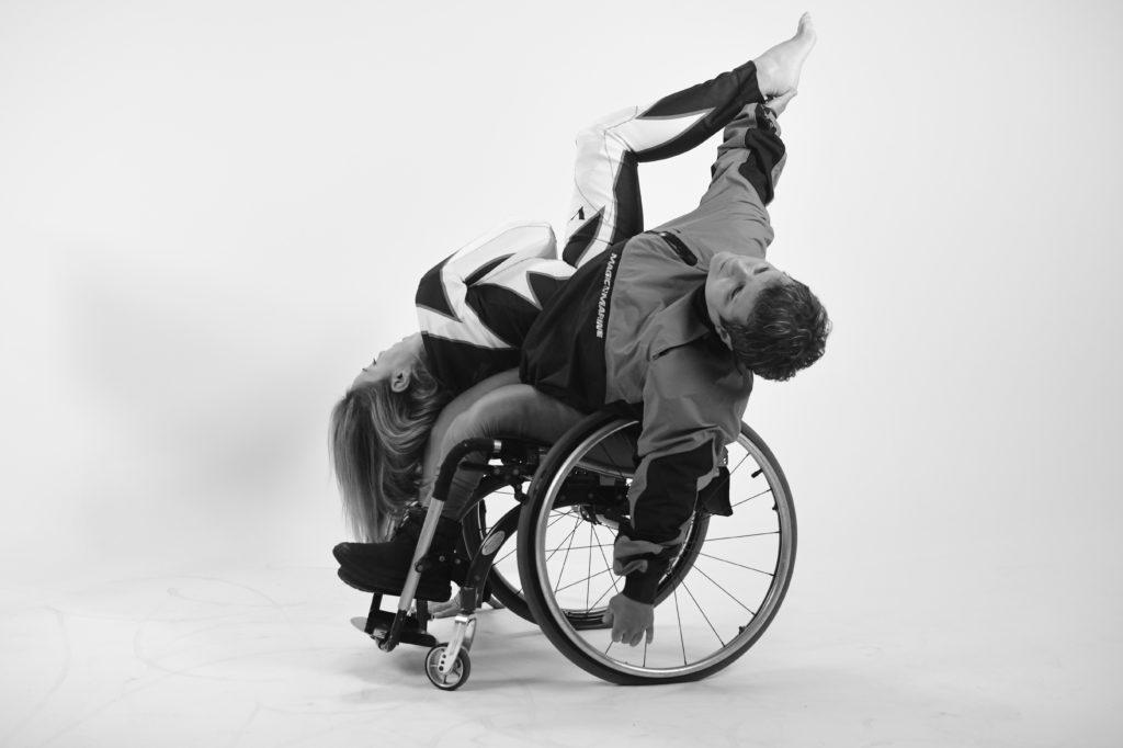 A female dancer in a wheelchair stretches one arm up that meets the other dancer's foot who is lying upside-down diagonally..