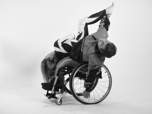 Two female dancers duet, one using a wheelchair and reaching with their hand straight up to catch the foot of the other dancer whose in an upside-down position
