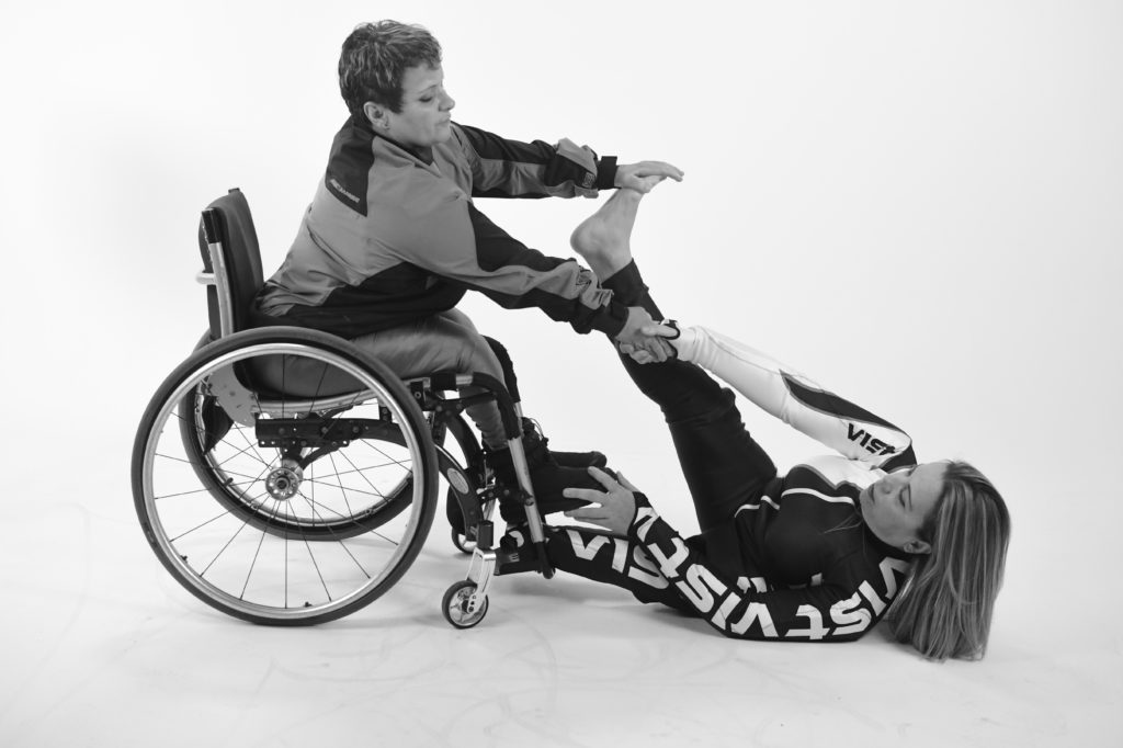 A female performer in a wheelchair flexes another performer's foot who is lying down on the floor.