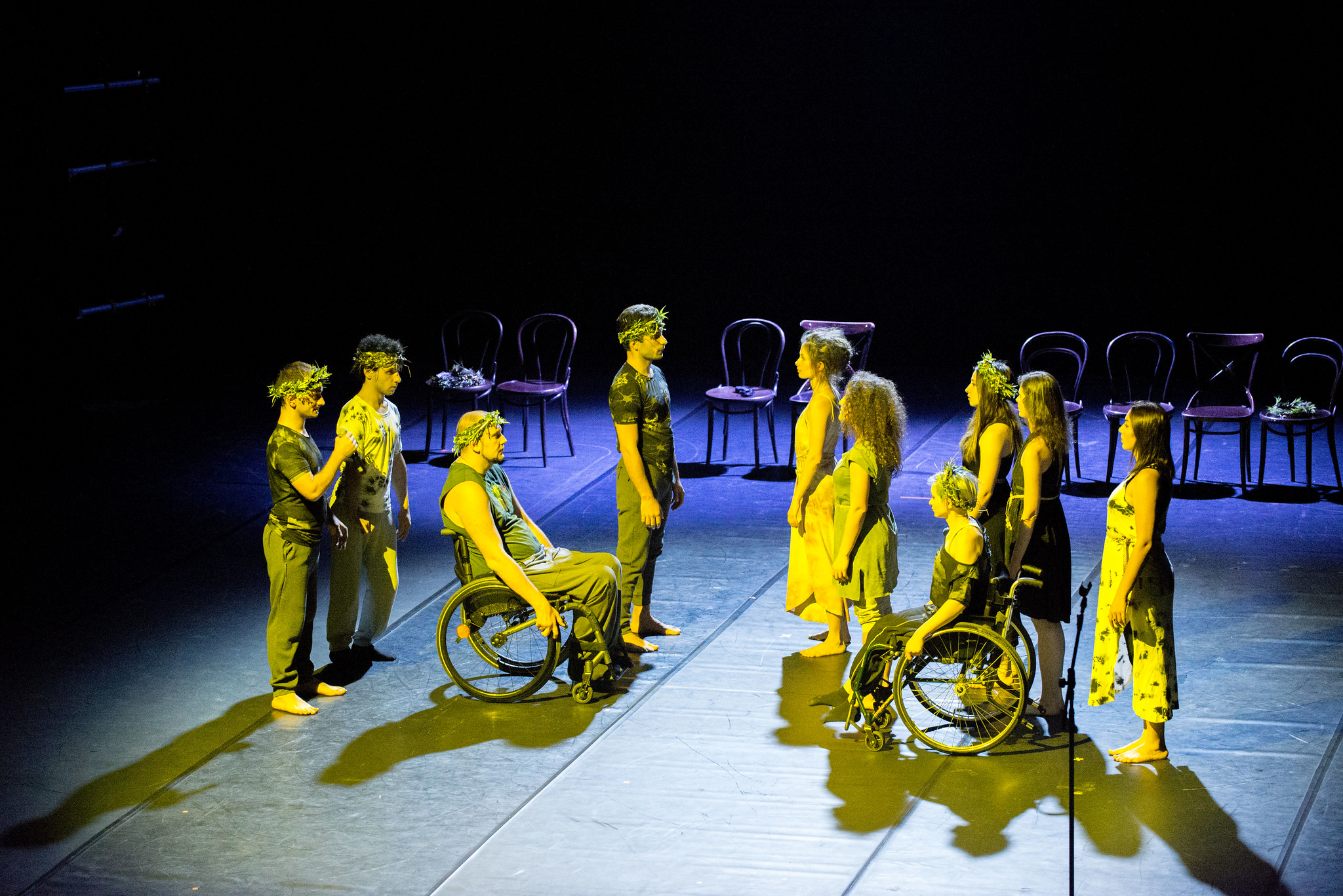9 disabled and non disabled performers illuminated with yellow lights on a blak stage