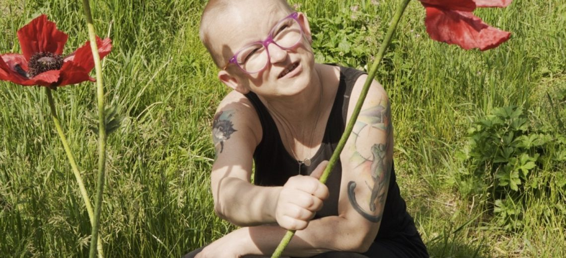 White woman with shaved head and glasses crouching in a field holding a red flower