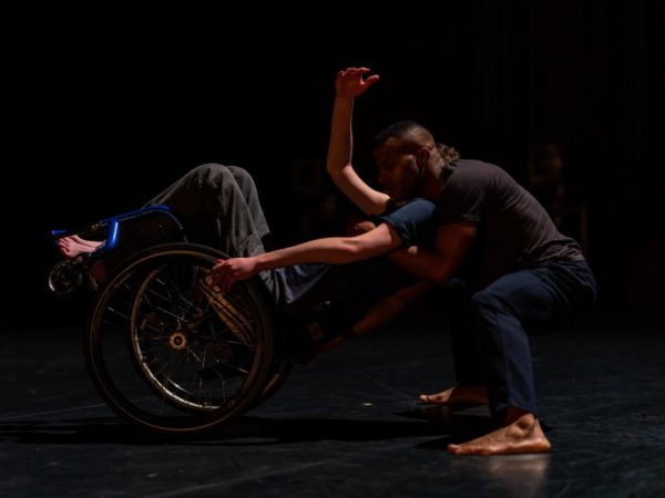 One dancer leans back in a blue wheelchair as another stands behind him to embrace his shoulders.