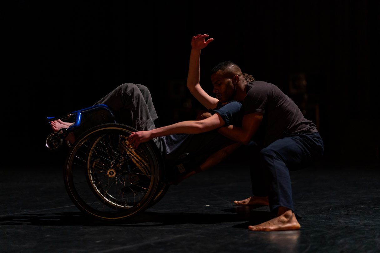Two male dancers, one leans back in a blue wheelchair, the others crouches low to the floor embracing his shoulders.