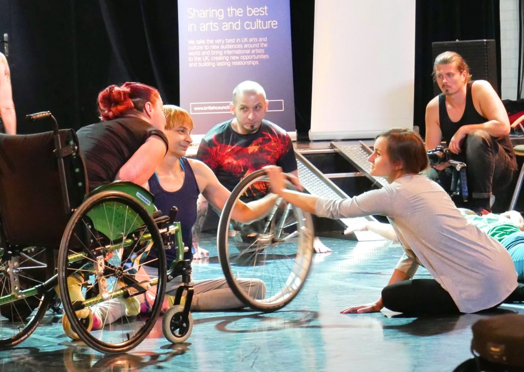 Tatiana sits on the floor having removed a wheel from a wheelchair and spins it with a female Deaf dancer