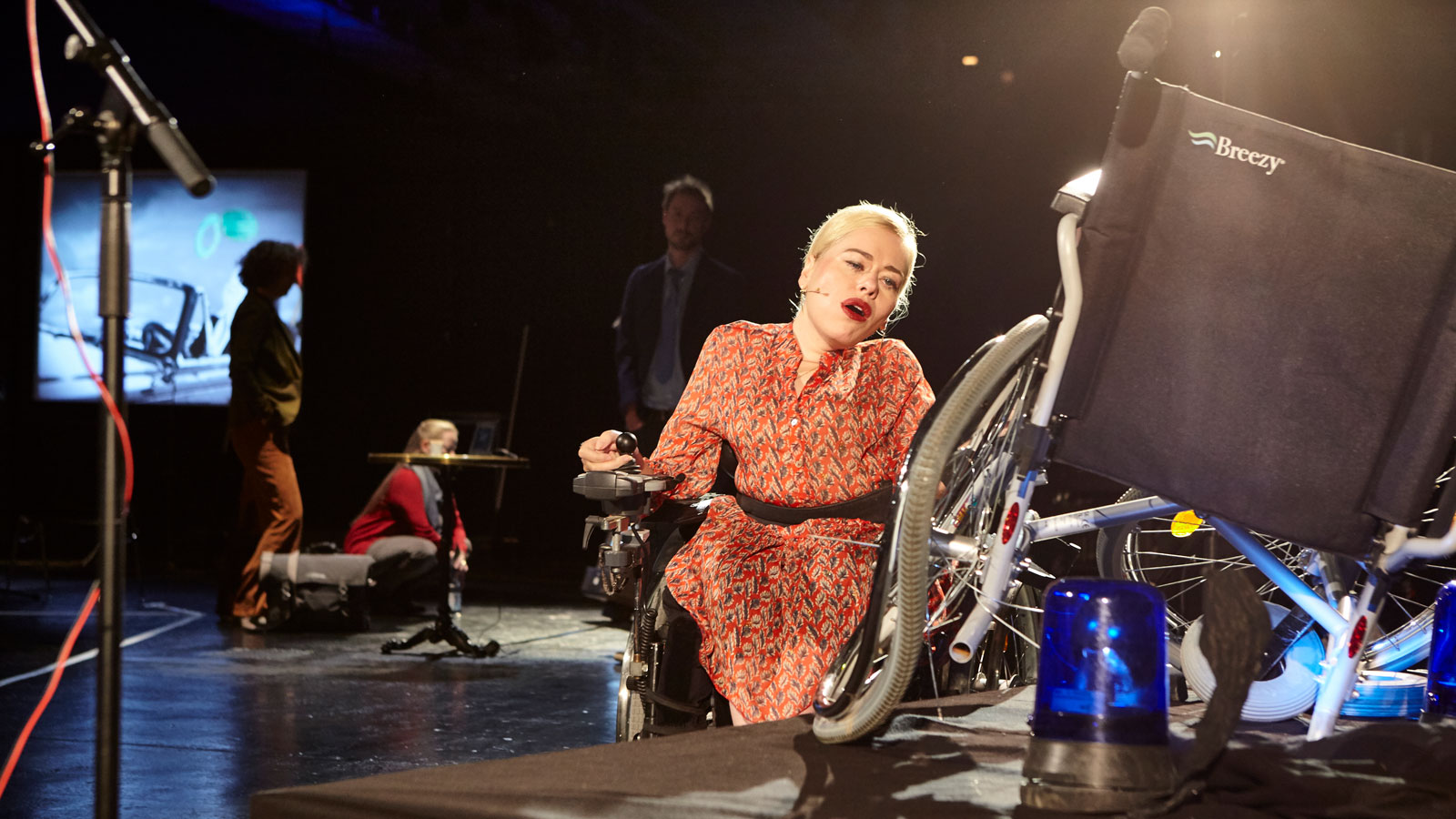 PErformer in a power-assisted wheelchair looks at a broken and mangled manual wheelchair