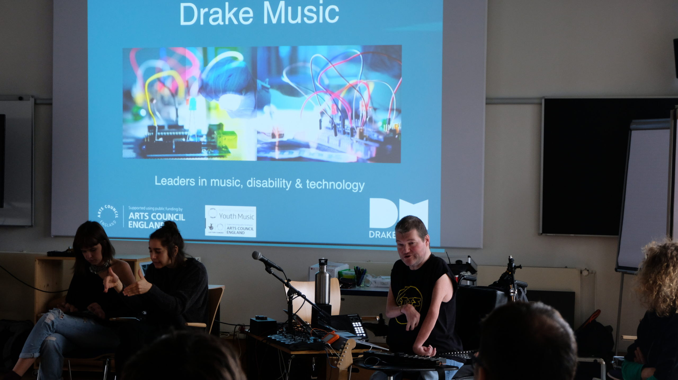 Wheelchair user presenting to a crowd whilst sat in front of music technology equipment with a projection behind him