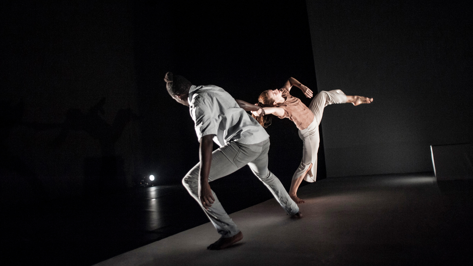 Black male and white female dancer holding each other by the hand and leaning backwards