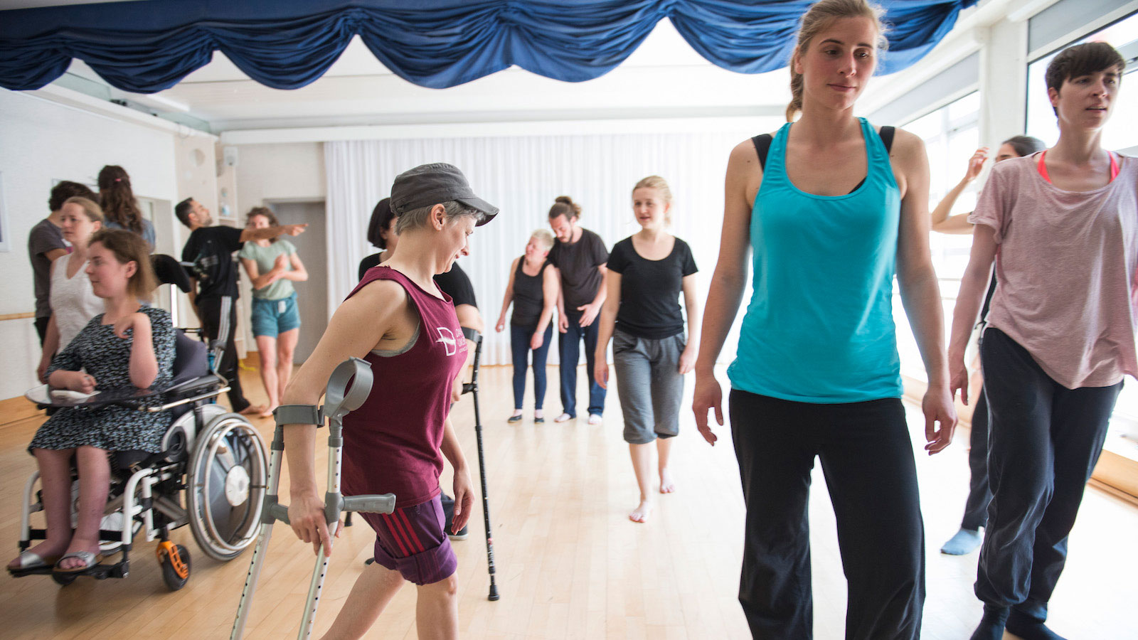 A mixed group of disabled and non-disabled performers take part in a dance masterclass