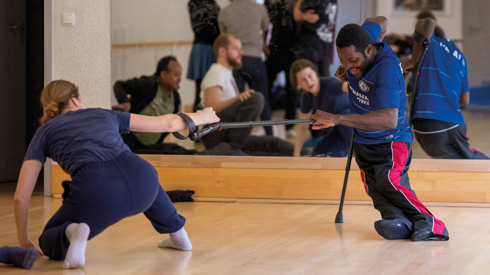 A black man and white woman take part in a dance masterclass using crutches