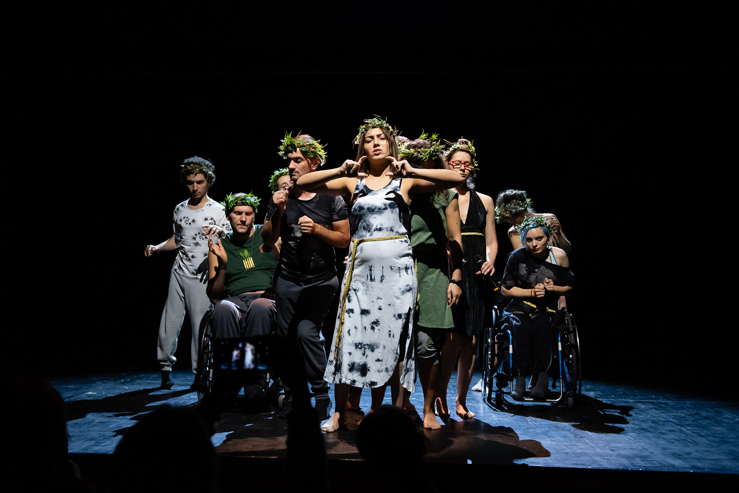 10 disabled and non-disabled performers standing on a stage huddled together, all of them are wearing olive wreaths on their heads