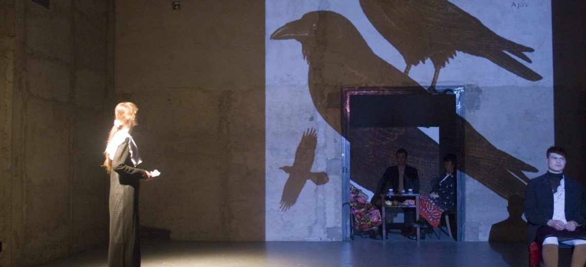 A subtle woman-girl on the scene watches a large-format projection of birds on the stage horizon