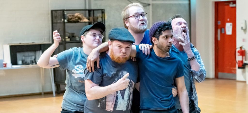 A cast of male actors in rehearsals holding each other in a huddle