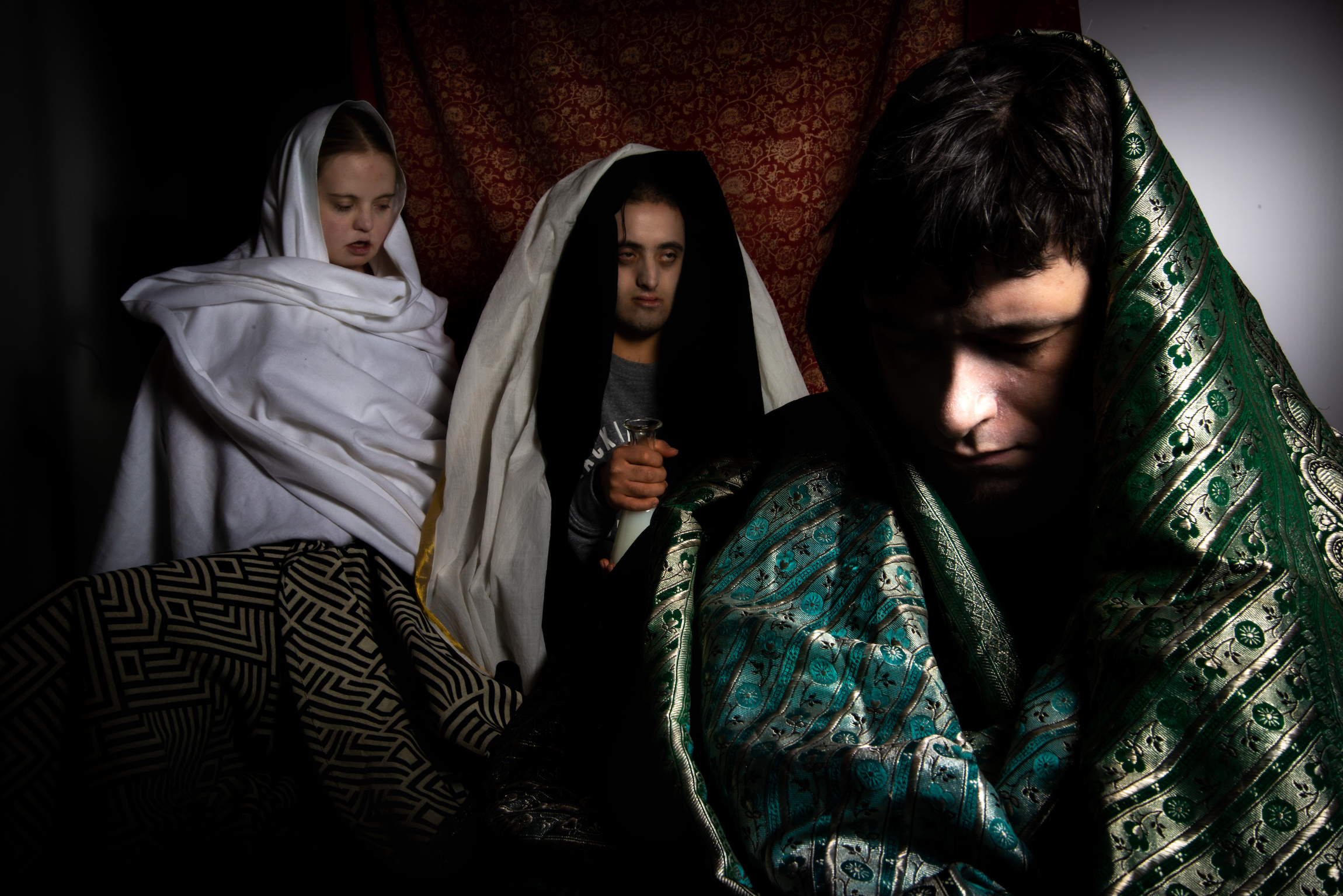 3 learning disabled people sit wrapped in shawls