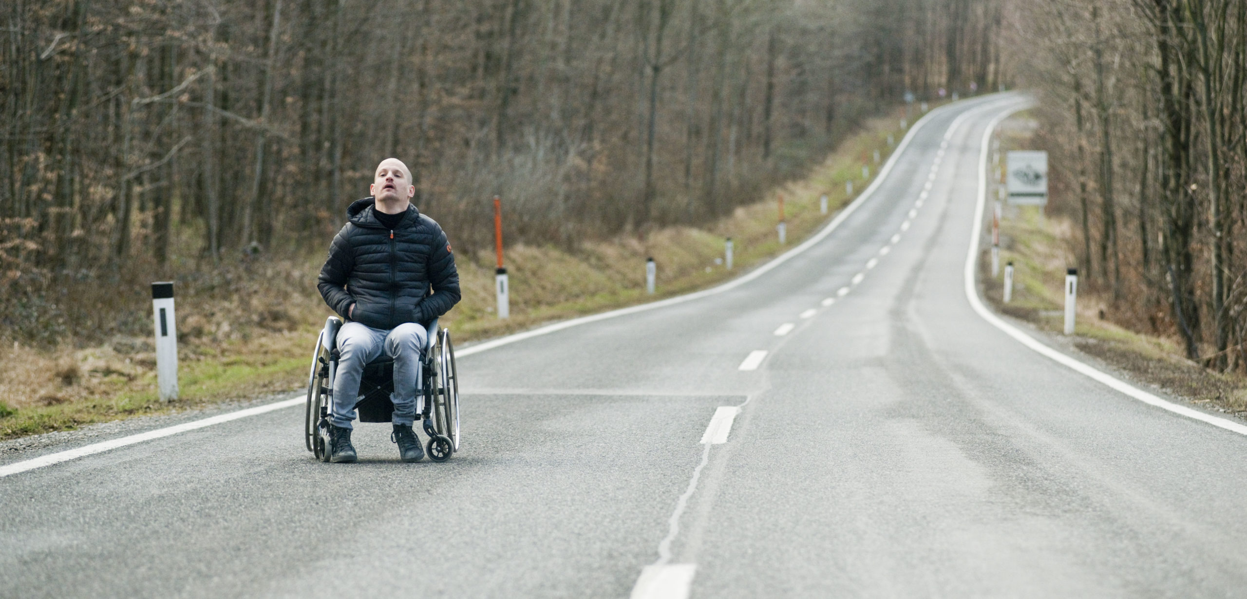 Man in wheelchair in the middle of an empty road