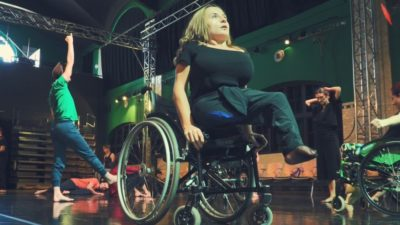 A female performer raises herself up from her wheelchair