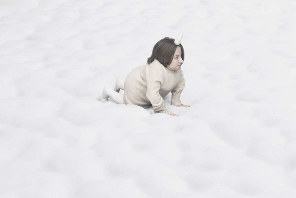 A small female performer all in white with a unicorn's horn crawls across a fluffy cloud landscape.