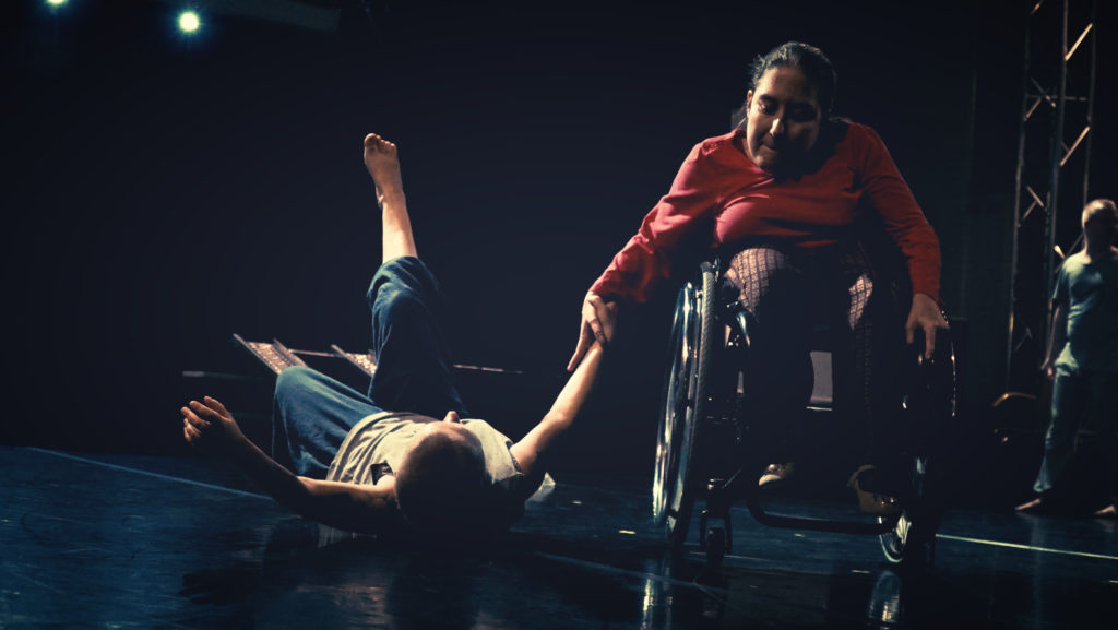 Two performers on a theatre stage, one woman in a wheelchair holds another woman's hand as she lies back on the floor with one leg in the air.