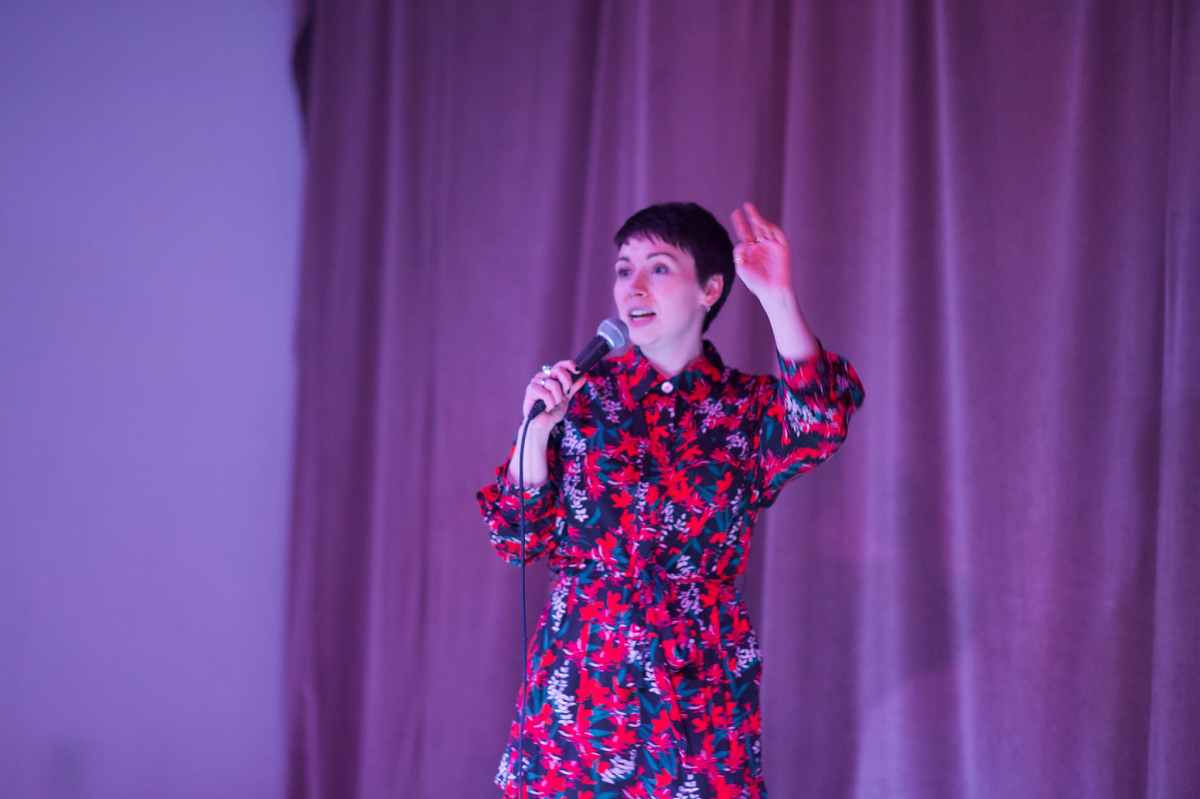 White woman with short dark hair doing stand up comedy, wearing a patterned red and blue outfit