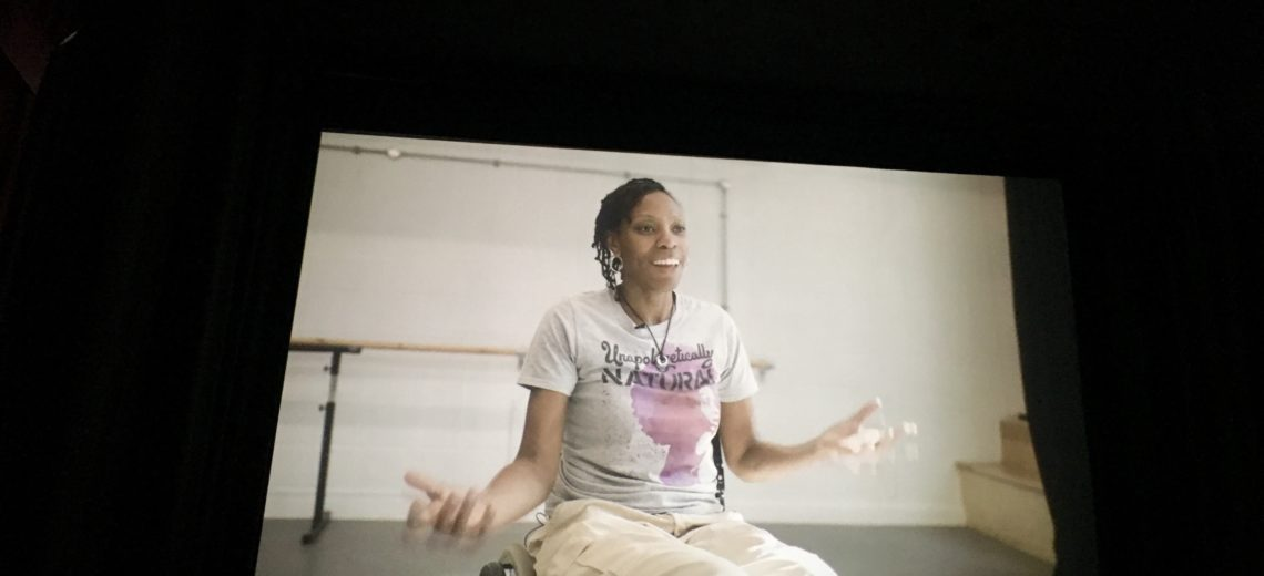 Image of cinema screen shows a female wheelchair dancer mid-interview