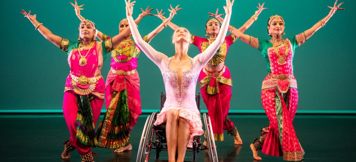Female wheelchair dancer framed by 4 dancers on stage