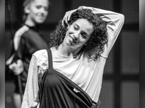 Black and white photo of a female dancer with dark curly hair. She reaches her arm up and over her head, smiling.