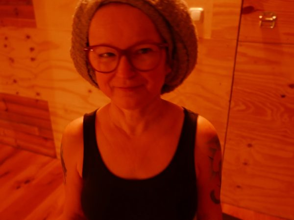 A woman with a knitted beanie hat, black top and glasses smiles