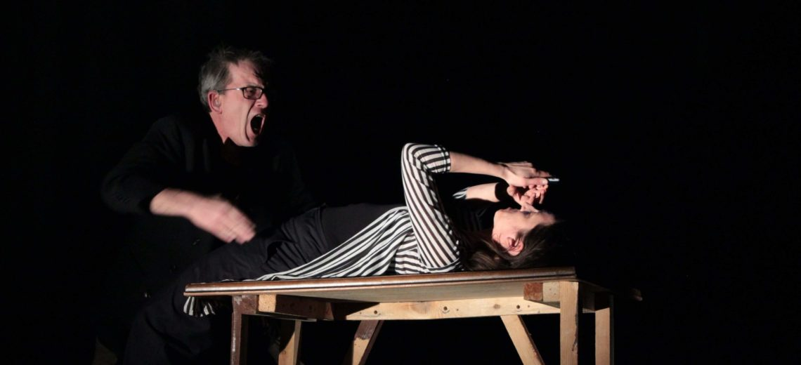 The performance is based on human trafficking . In this photo we see the situation where the woman who is being trafficked is being shouted at . She lays on a table with her hands held over her face