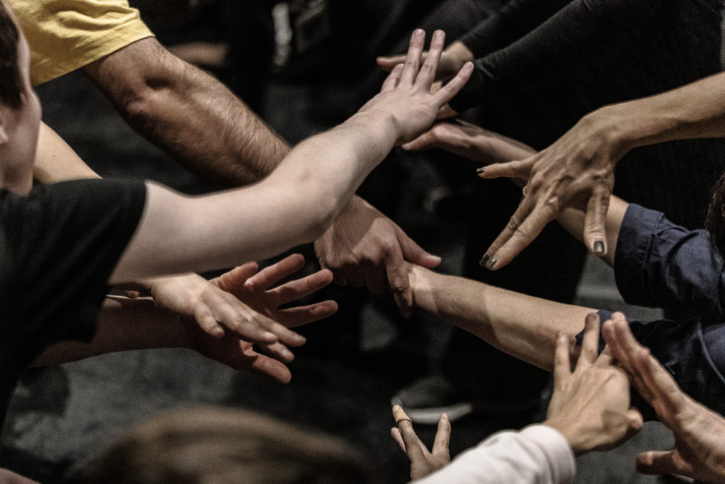 Multiple hands all gather together, reaching and stretching towards one another.